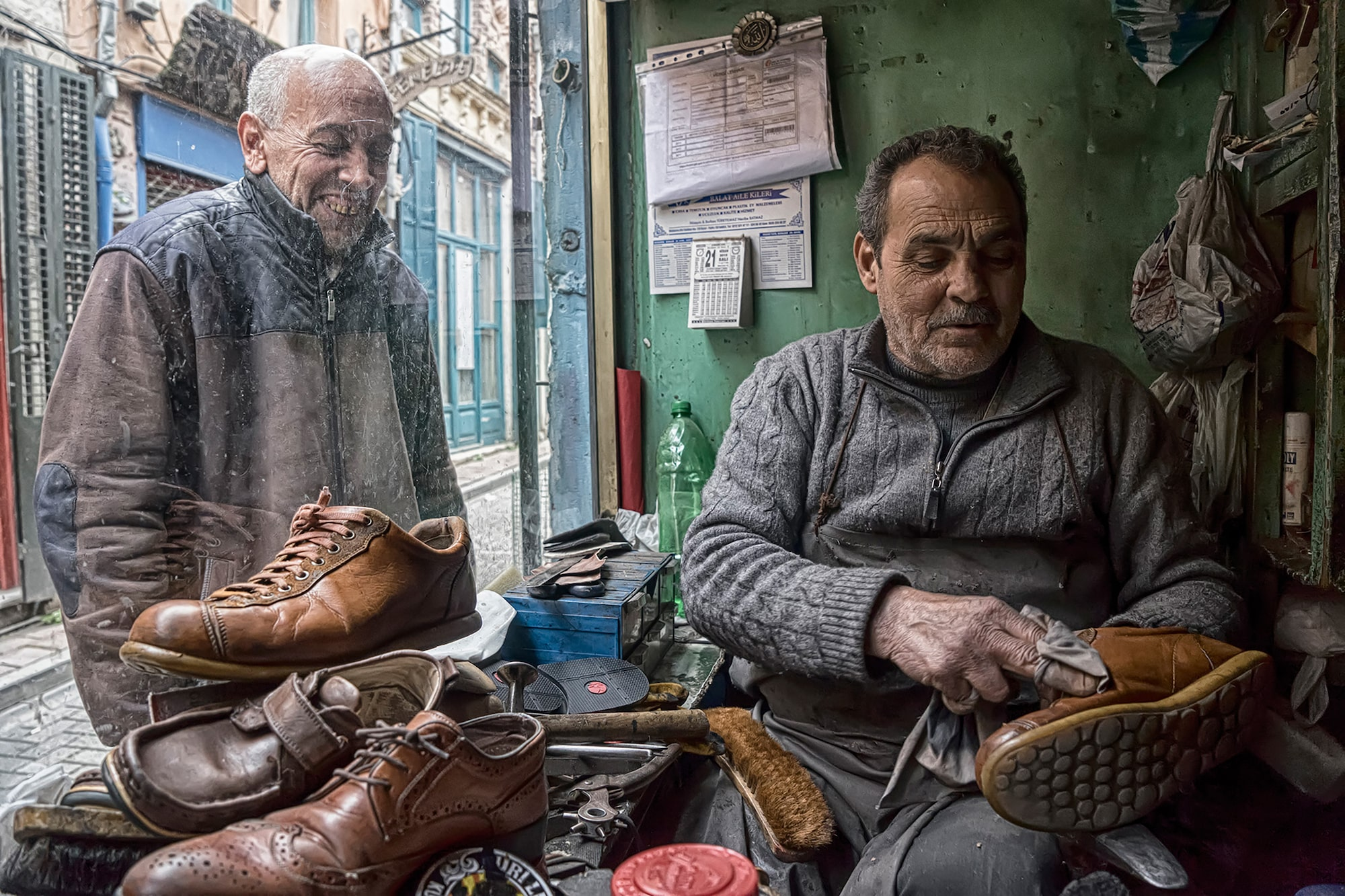 murat pulat sony alpha 7II a cobbler sits and rubs polish into a show while an old man looks through the window