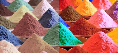 Piles of brightly mutlicoloured sand showing Triluminos PRO colour range