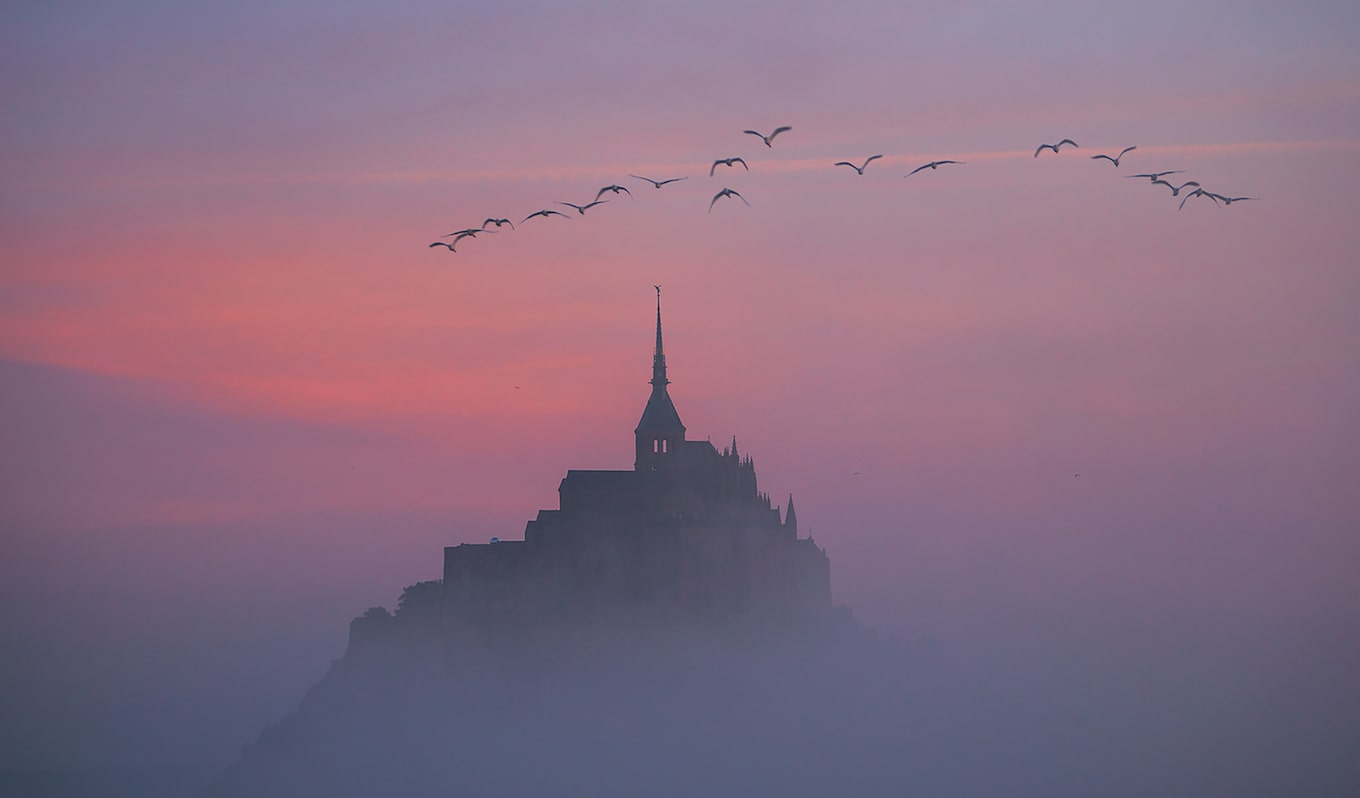 ilhan-eroglu-sony-alpha-7R-mont-saint-michel-in-silhouette-with-birds-flying-over