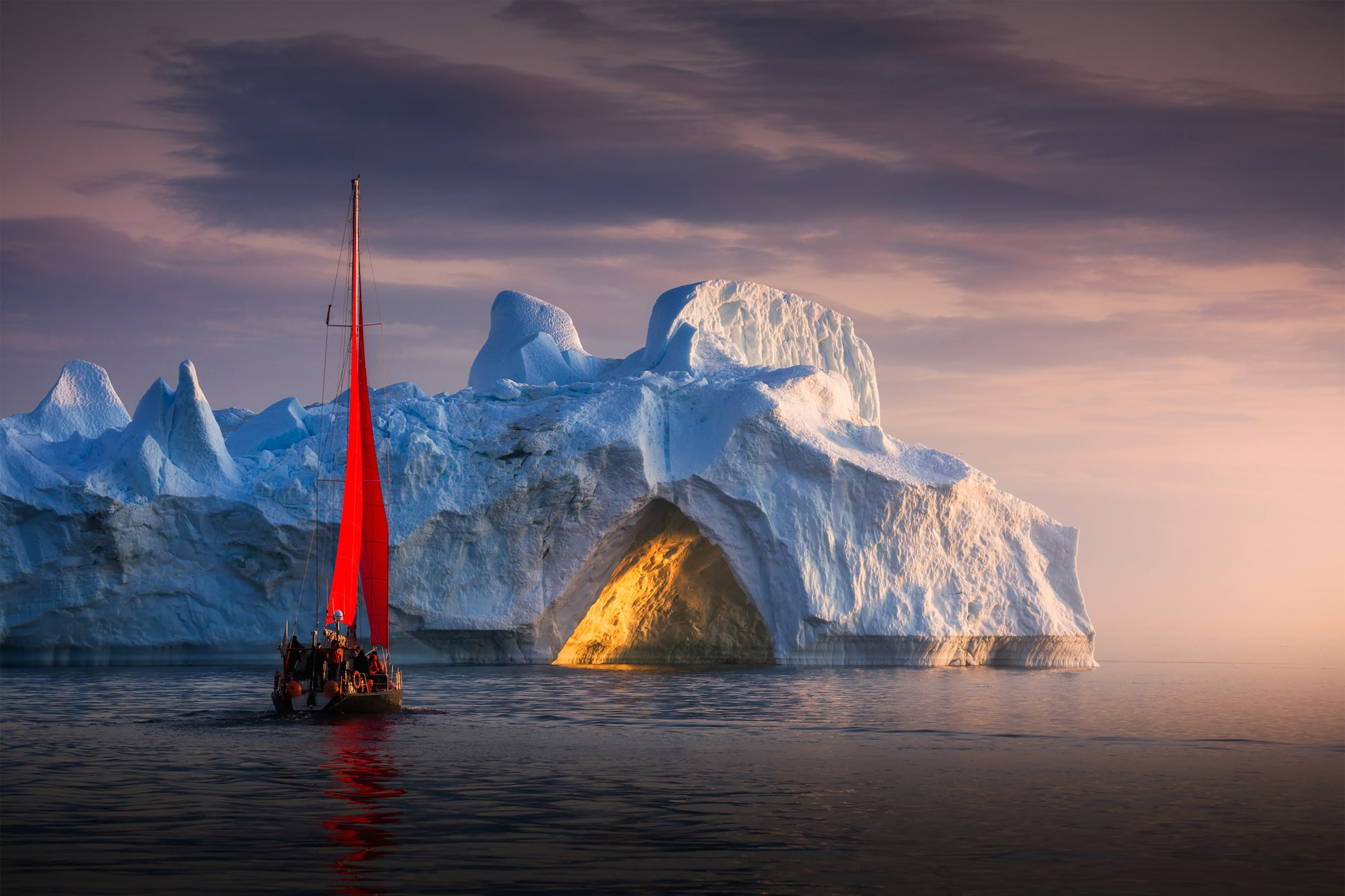 albert dros sony alpha A7RM4 a sailing ship sits in front of an iceberg with the late evening sun casting a warm glow through a natural cave