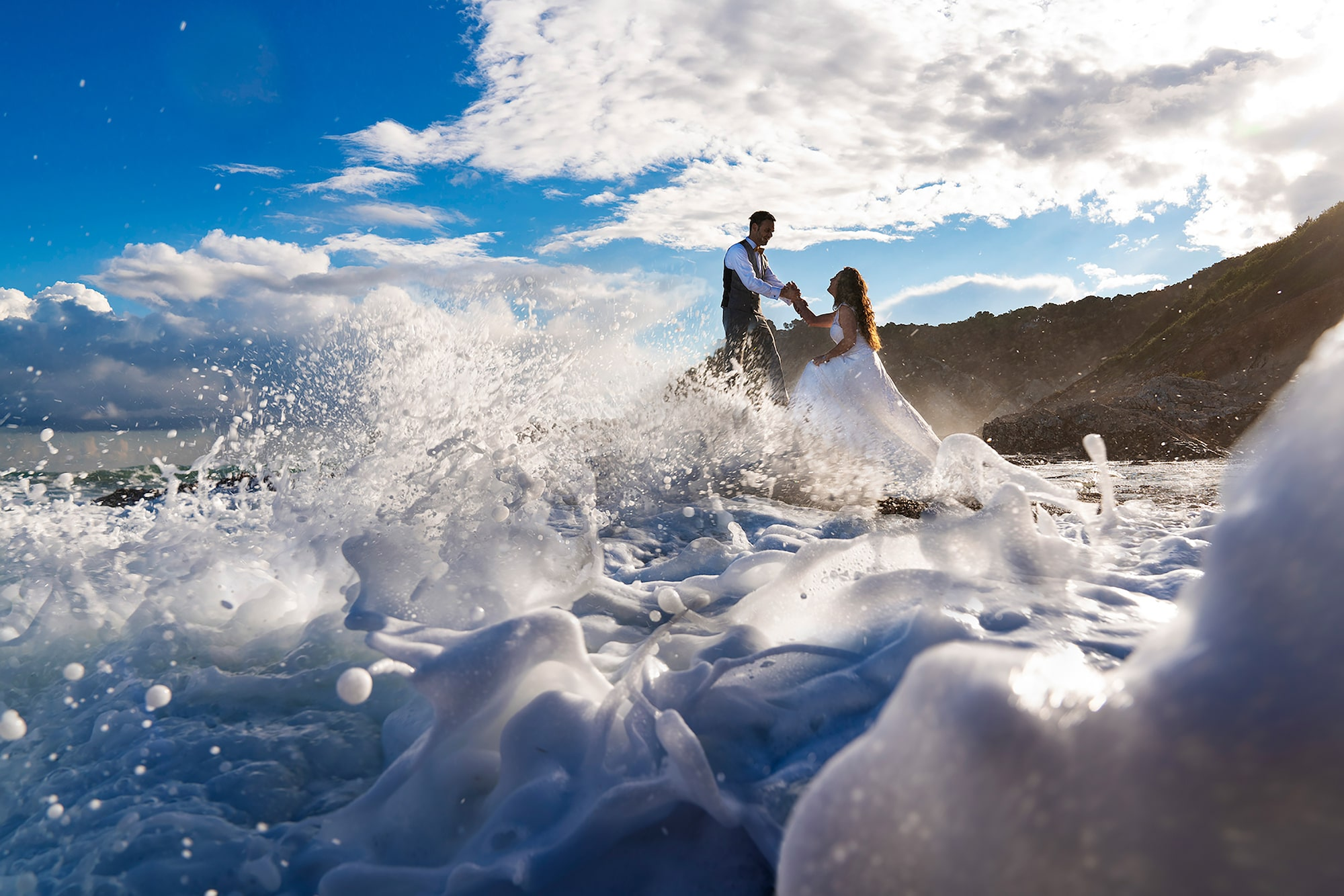 jorge miguel jaime baez sony alpha 7RIII bride and groom standing in the ocean as waves rise before them