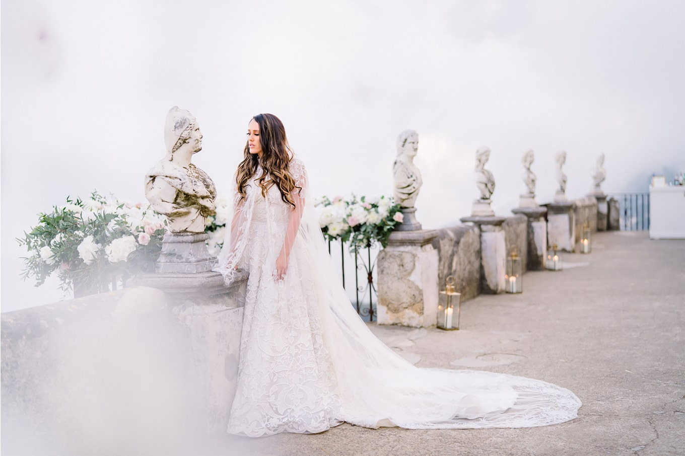 sandra aberg sony alpha 7r3 the bride wears her white dress and a veil cape while standing on a decorated terrace