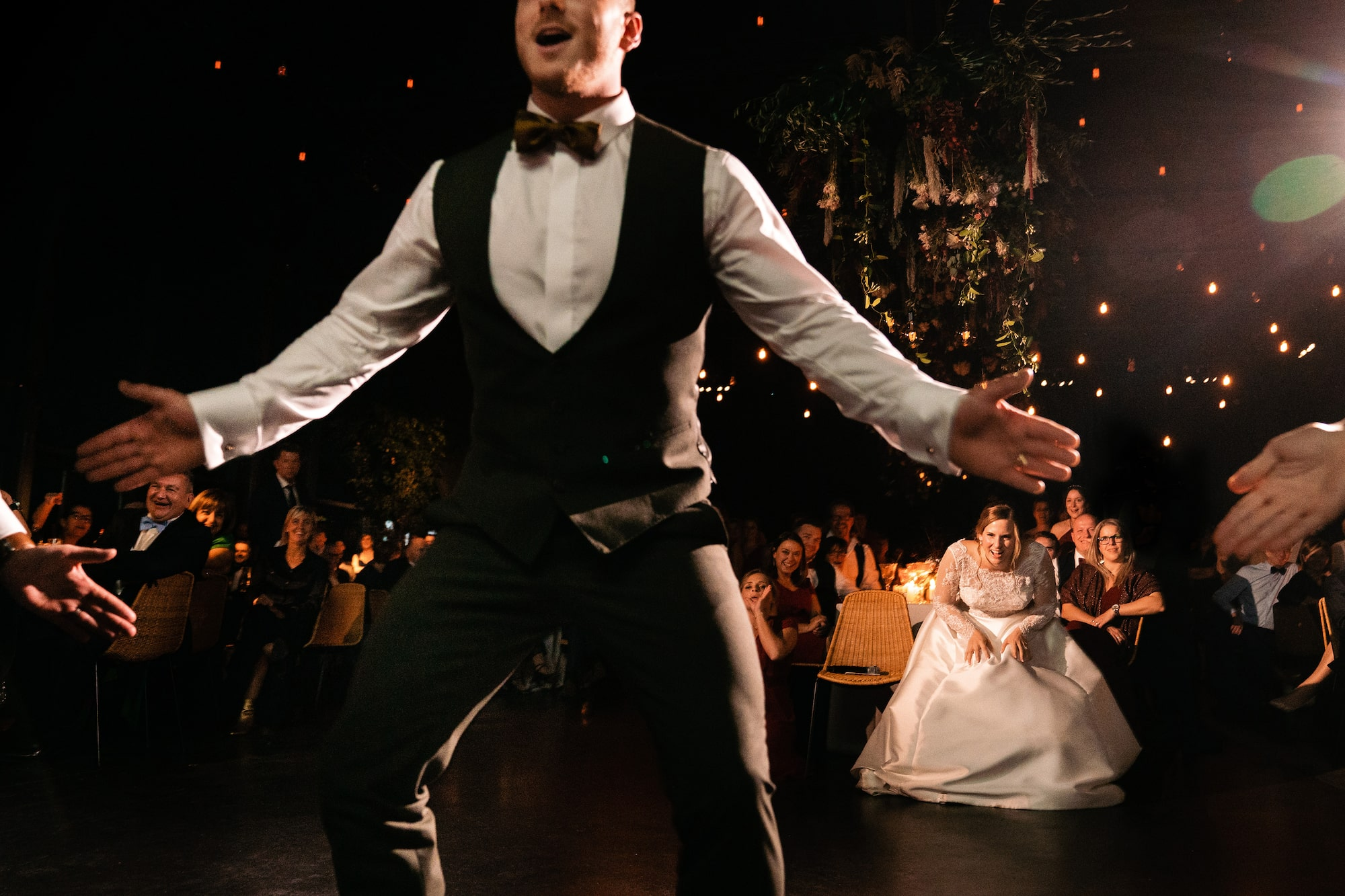 yves schepers sony alpha 9 groom on the dance floor as his bride crouches behind watching him