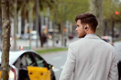 Lifestyle image of man walking along wearing WF-1000XM3 headphones
