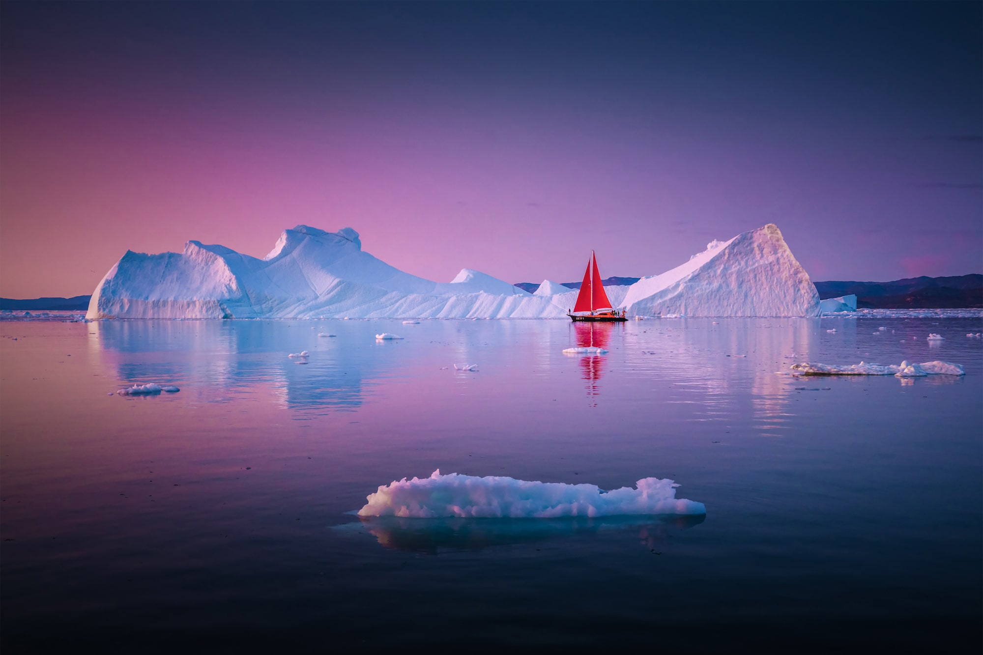albert dros sony alpha A7RM4 an iceberg framed perfectly in front of a soft red sunset in greenland.