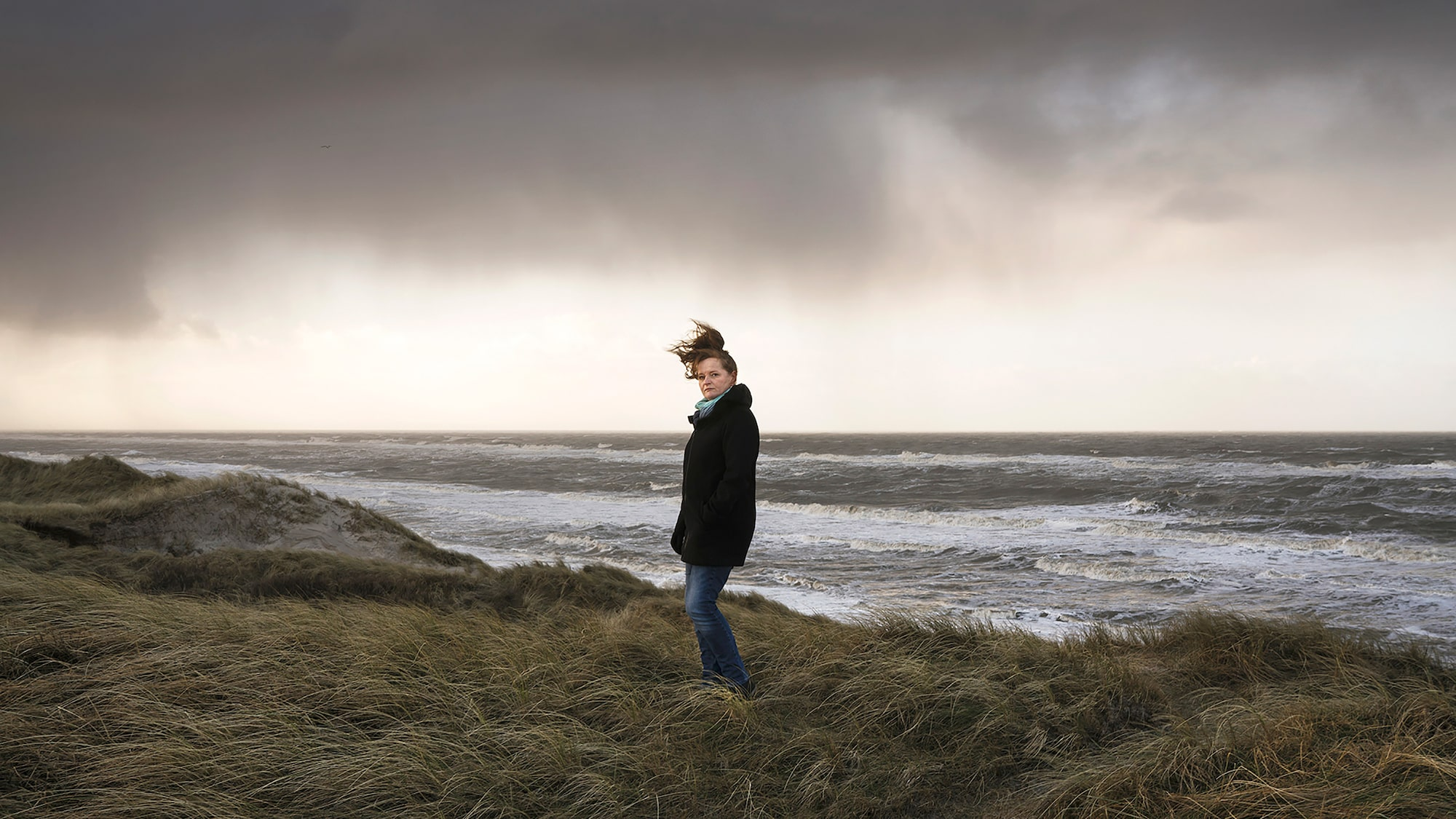 laerke posselt sony alpha 7R II a lady standing on a windy cliff top looking at the camera