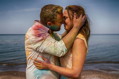 marcis baltskars sony a7rIII bride and groom in paint splattered clothes kiss on a beach