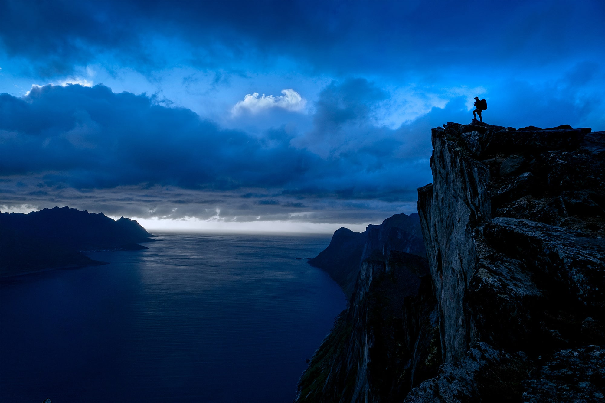 daniel ronnback sony alpha 9 silhouetted man standing on a clifftop against a blue dusk sky