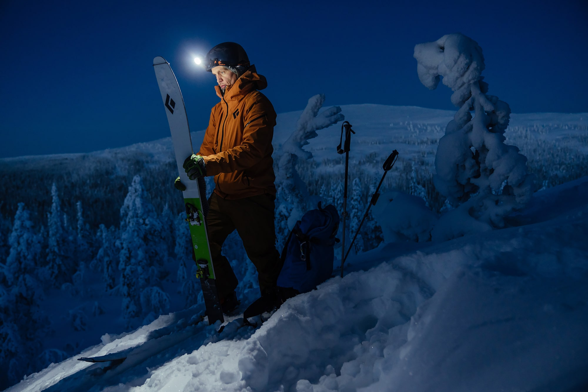jaakko posti sony alpha 9 skier inspects his ski with the help of a head torch