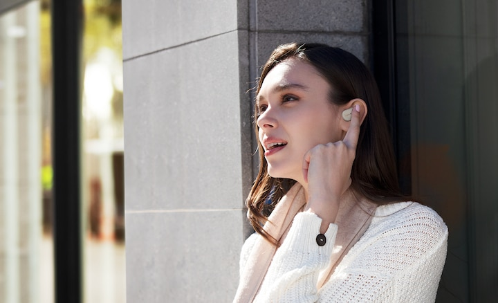 Lifestyle image of woman using Voice Assistant on WF-1000XM3 headphones.