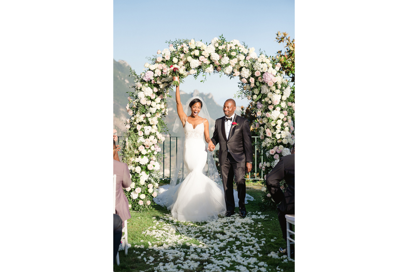sandra aberg sony alpha 7r3 grooms stand in front of a flower arch and bride raises her bouquet