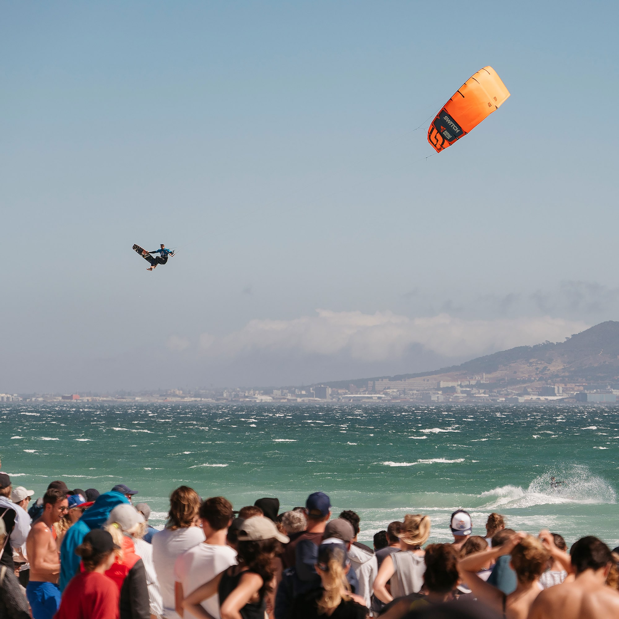 danas macijauskas sony alpha 7III kite surfer high above the ocean as a crowd watch in the foreground