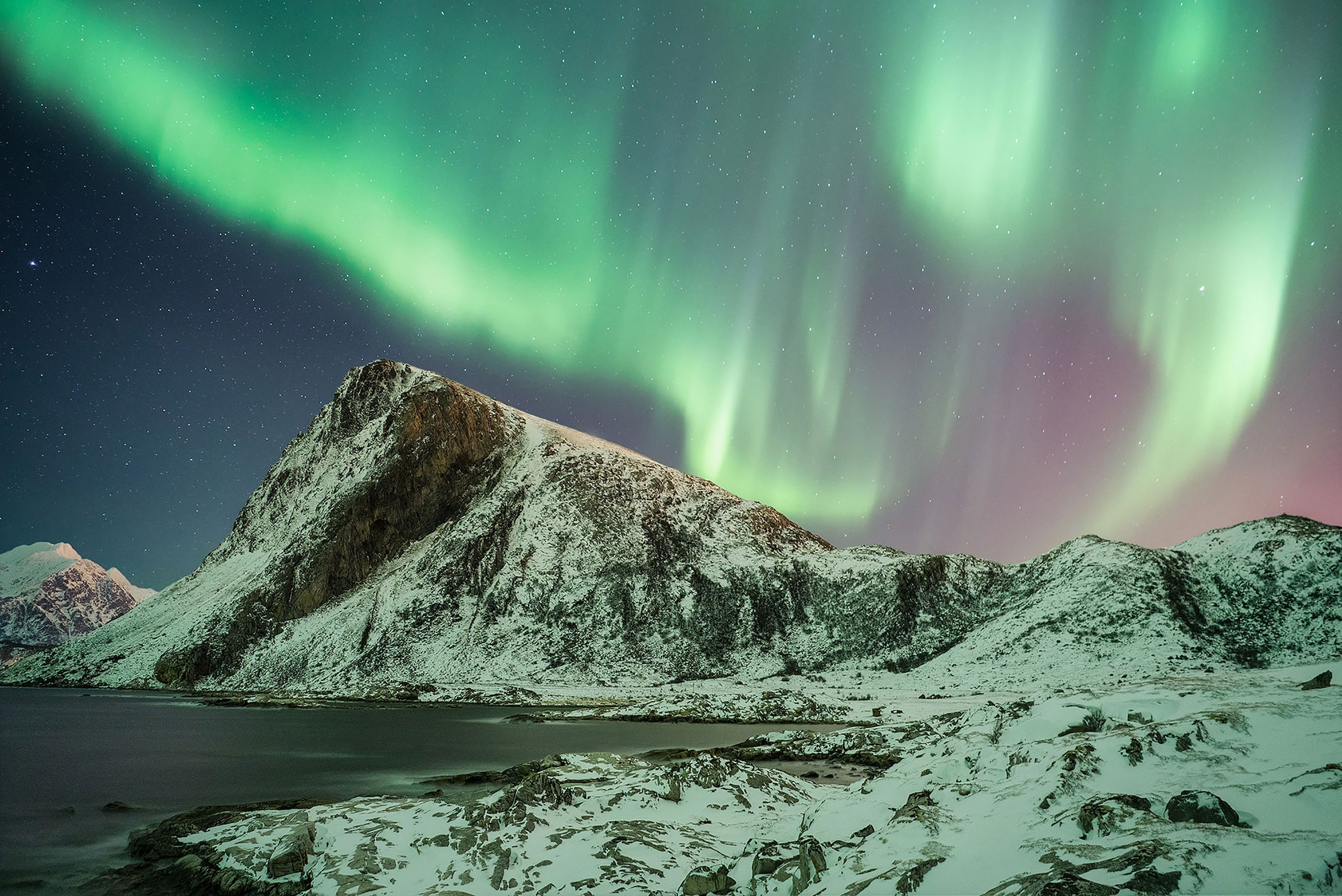 michael schaake sony alpha 7RIII the aurora borealis dancing in the sky behind snowy mountains