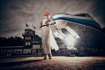 frank doorhof sony alpha 7RII lady wearing a silver dress standing in front of an aeroplane