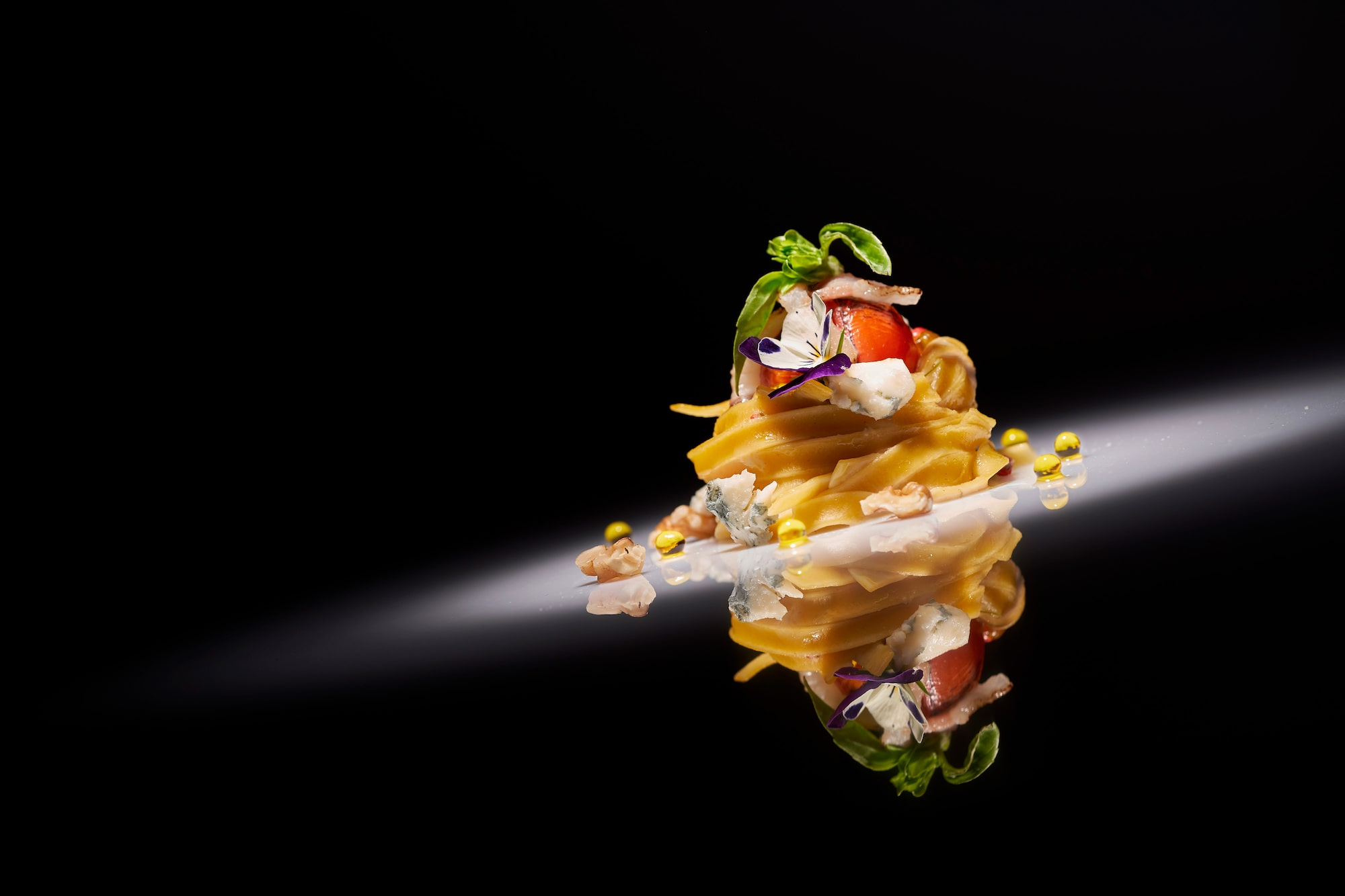 pablo gil sony alpha 7RM3 pasta topped with tomato on corn postioned on a reflective plate and lit with a spotlight