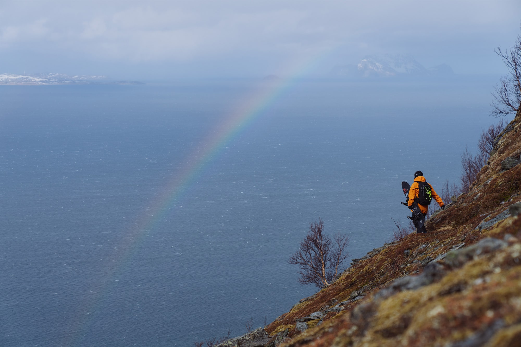 jaakko posti sony alpha 7RM3 man stands on a remote mountainside gazing across the sea with a rainbow visible across the frame