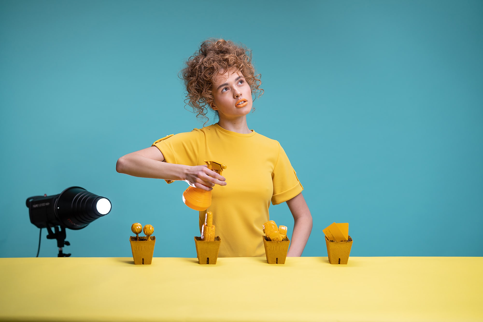 virgo haan sony alpha 7RII lady wearing a yellow teeshirt in front of a yellow table holding a matching water sprayer