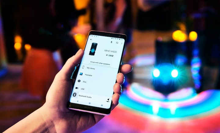 Partygoer using Sony | Music Center app on their smartphone