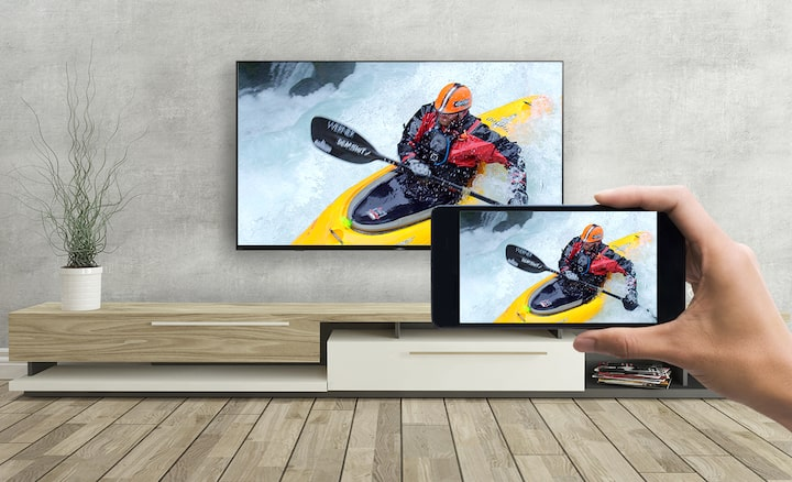 Person holding a smartphone with image of canoeist cast to a TV wall mounted above a wooden cabinet