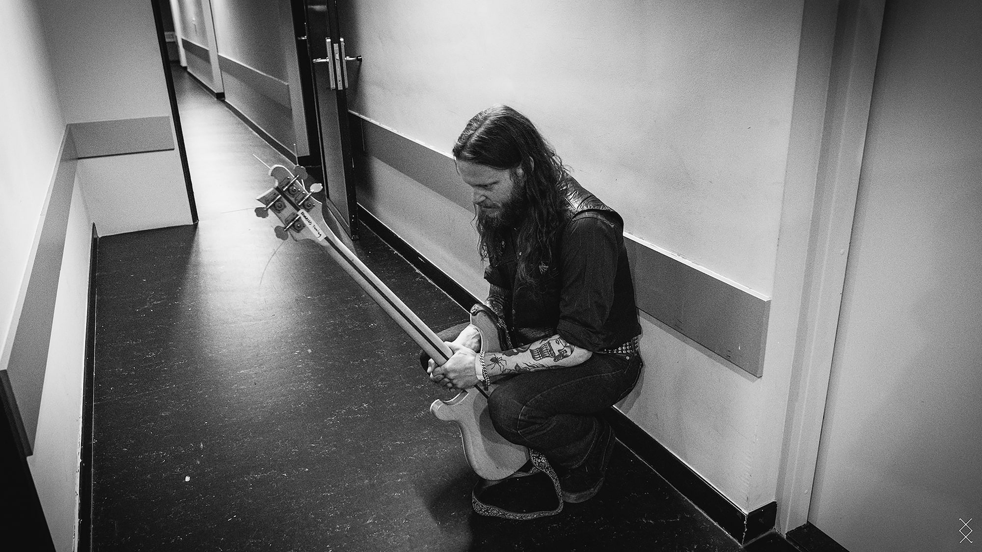 maaike ronhaar sony alpha 7RIII bass guitarist sits on his haunches waiting to go on stage