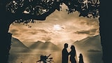 cristiano-ostinelli-sony-alpha-9-bride-and-groom-silhouetted-in-front-of-ocean-about-to-kiss